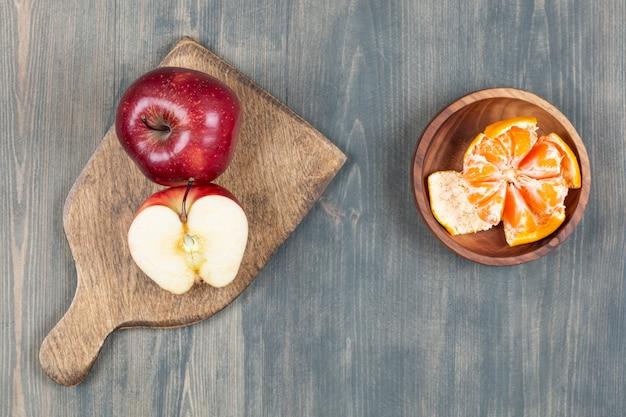 Rode appel op houten bord met kom mandarijnsegmenten