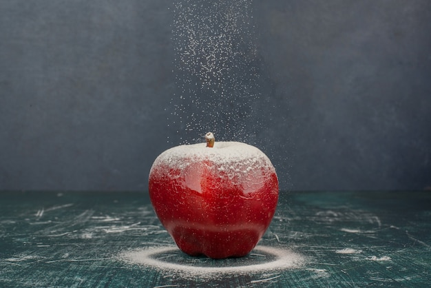 Rode appel versierd met poeder op blauwe achtergrond.