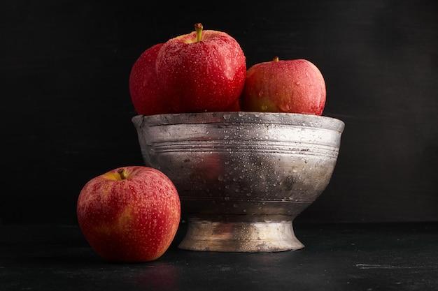 Rode appels in een metalen beker op zwarte ondergrond.