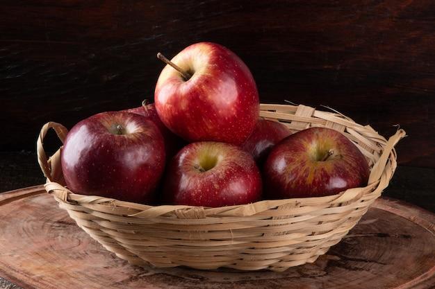 Rode appels in mand met houten achtergrond