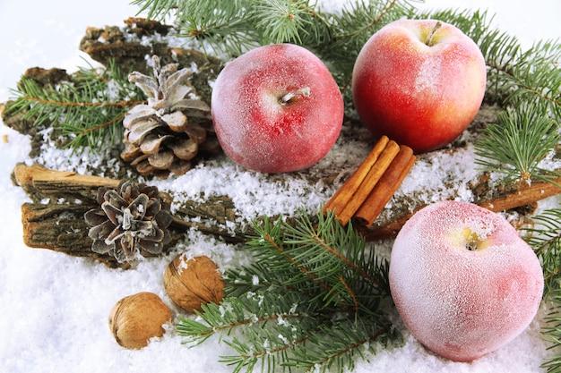 Rode appels met dennentakken op schors in sneeuw close-up