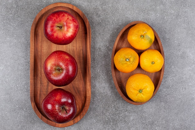 Rode appels met zoete mandarijnen op een houten bord