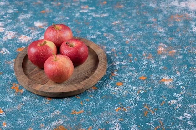 Rode appels op houten schotel op blauw.