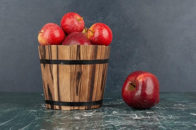 Rode appels vallen uit de emmer op marmeren tafel.