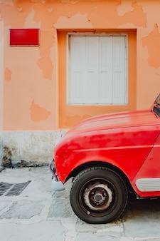 Rode auto door oranje muur