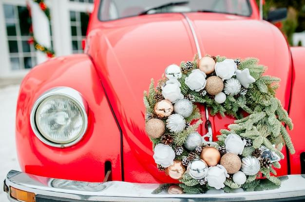 Rode auto in de sneeuw met kerstcadeaus op het dak en een krans. nieuwjaarskarweien.