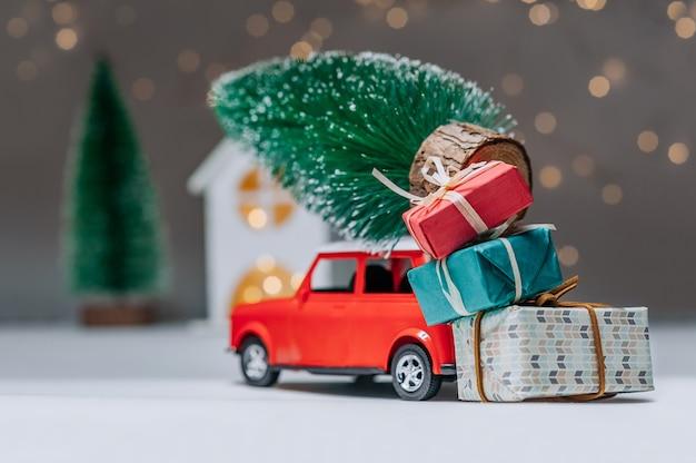 Rode auto met een kerstboom op het dak. tegen de achtergrond van het huis. concept rond het thema kerstmis en nieuwjaar.