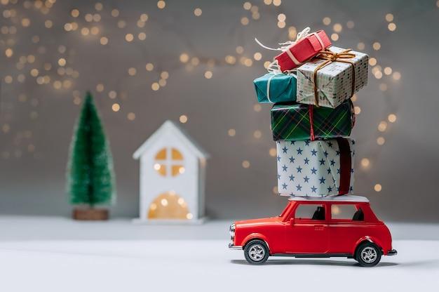 Rode auto met geschenken op het dak. tegen de achtergrond van het huis en de boom. concept rond het thema kerstmis en nieuwjaar.