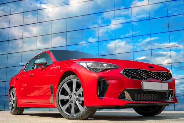 Rode auto op een blauwe hemelachtergrond met witte wolken.