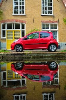 Rode auto op kanaaldijk in straat van delft delft nederland