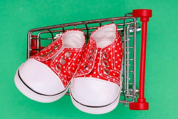 Rode babyschoentjes met witte stippen in een supermarktwagen op groen