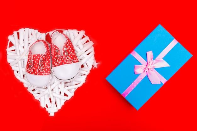 Rode babyschoentjes met witte stippen op een rode achtergrond met cadeautjes