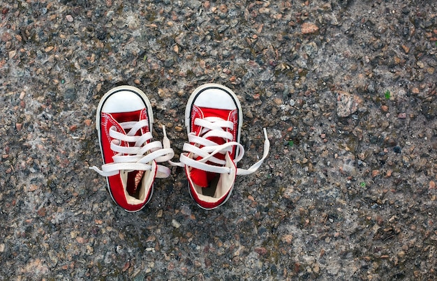 Rode babysneakers op asfalt
