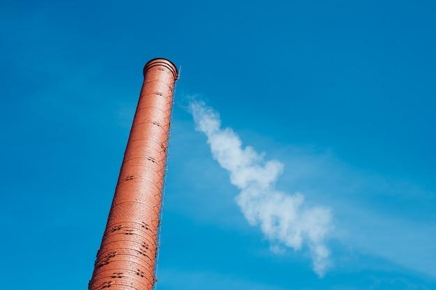 Rode baksteenschoorsteen met rook op blauwe hemel