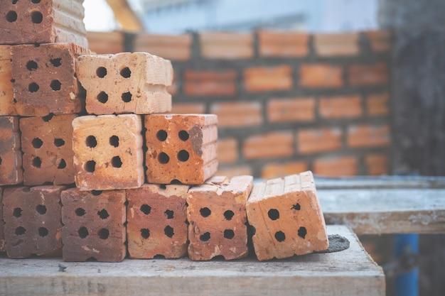 Rode bakstenen die voor bouw op bakstenen muur worden gebruikt