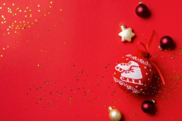 Rode bal met patroon voor de kerstboom met gouden confetti en speelgoed op een rode achtergrond. bovenaanzicht