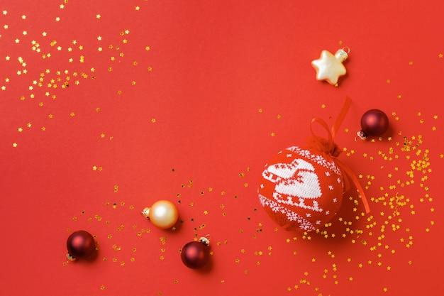 Rode bal met patroon voor de kerstboom met gouden confetti en speelgoed op een rood. minimale kerststijl en vakantieconcept.