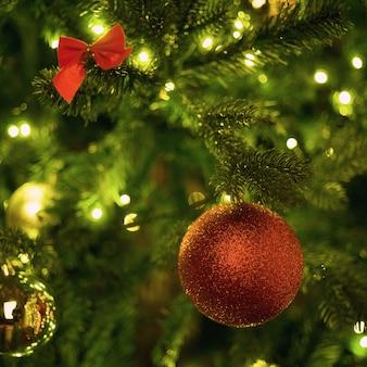 Rode bal op een kerstboom met een slinger op de achtergrond van een houten muur
