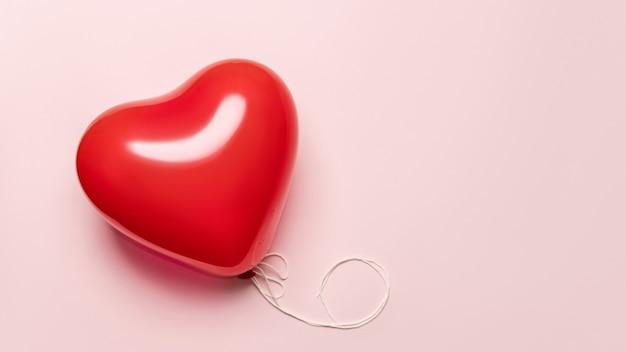 Rode ballon in vorm van hart op bleek - roze achtergrond. valentijnsdag concept.