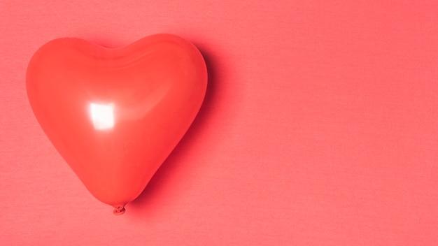 Rode ballon op rode achtergrond met kopie ruimte