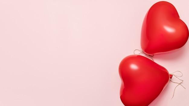 Rode ballonnen in de vorm van hart op bleke roze achtergrond. valentijnsdag concept. banner, kopieer ruimte
