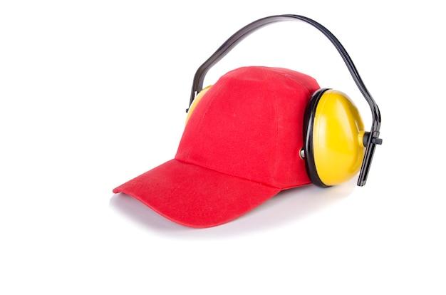 Rode baseball cap met lawaai koptelefoon op wit wordt geïsoleerd