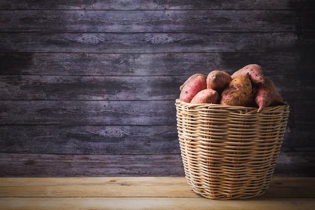 Rode bataten in mand, ruwe voedselvertoning op houten lijstachtergrond met exemplaarruimte