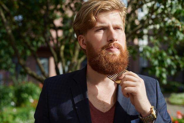 Rode bebaarde hipster in zomertijd wandelen en zijn baard kammen