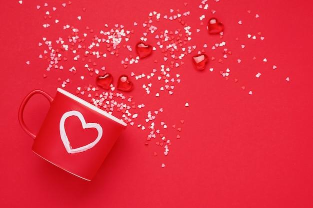 Rode beker mok met met geschilderde hart, suiker en chocolade hartjes op scharlaken of rode achtergrond. plat lag samenstelling. valentijnsdag concept. bovenaanzicht, kopieer ruimte.