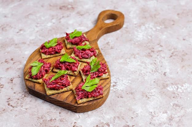 Rode biet hummus canapes met groene peper plakjes en peterselie op snijplank op lichte ondergrond