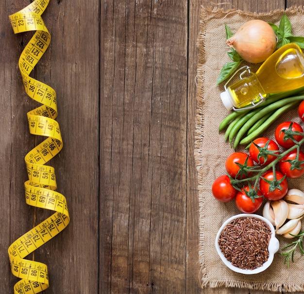 Rode biologische rijst, rauwe groenten en kruiden op houten tafelblad bekijken met kopie ruimte