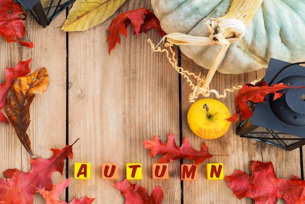 Rode bladeren, appel met lamp en gekleurde blokjes met herfst-inscriptie