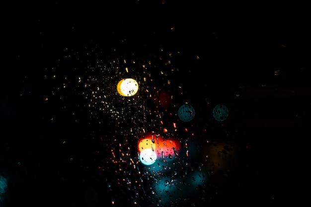 Rode blauwe en gele lichte bokehpunten op donkere achtergrond