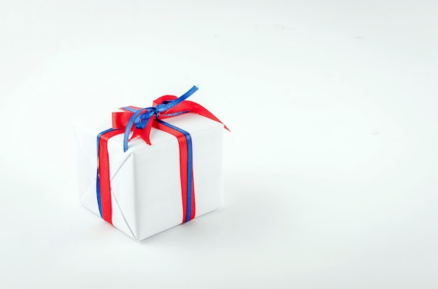 Rode, blauwe en witte geschenkdozen met linten op een witte achtergrond