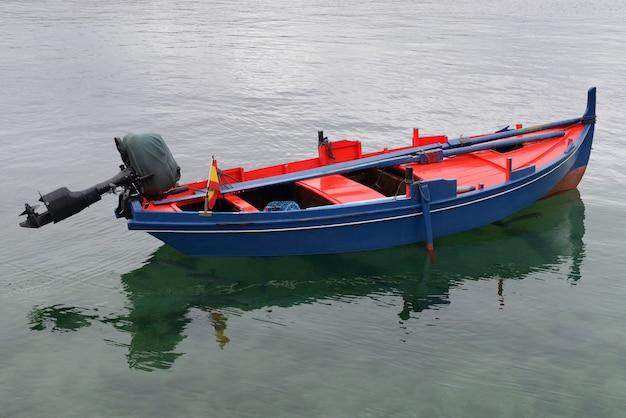 Rode blauwe houten vissersboot met motor afgemeerd in de zee