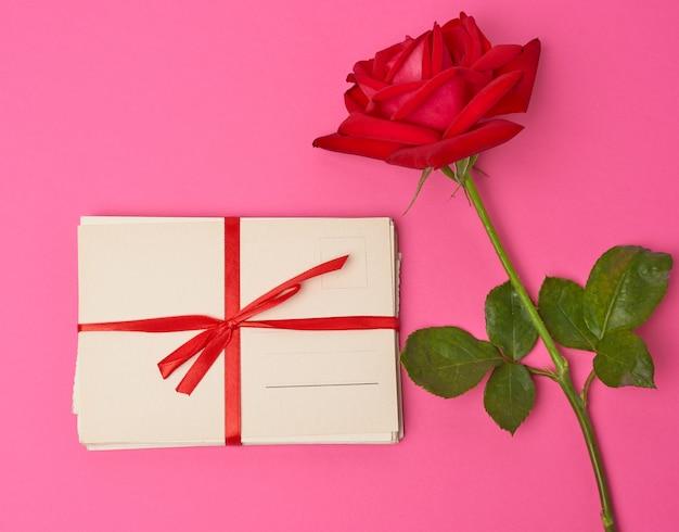 Rode bloeiende roos, stapel vintage papieren kaarten op een roze ruimte