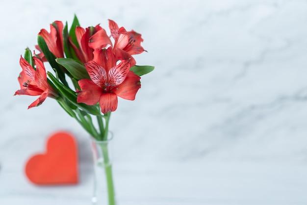 Rode bloemen en een rood hart op een witte houten achtergrond. wenskaart voor 14 februari. close-up met ruimte voor tekst. liefde concept