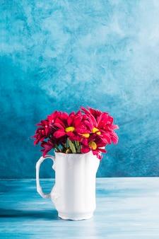 Rode bloemen in kruik op tafel