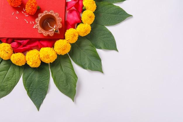 Rode boekhoudingsnotitieboekje, diya en bloemrangoli op wit