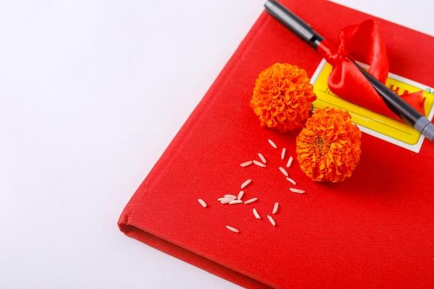 Rode boekhoudkundige nota boek en bloemen