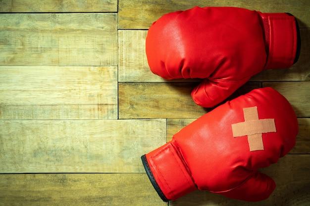 Rode bokshandschoenen die op houten vloer bij de gymnastiek worden geplaatst