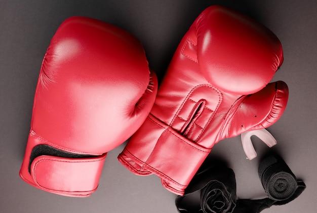 Rode bokshandschoenen en verbanden op een donkere achtergrond