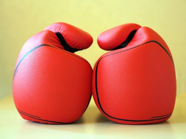 Rode bokshandschoenen op gele achtergrond.