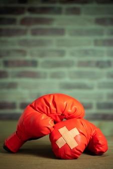 Rode bokshandschoenen op houten lijst en bakstenen muur bij de sportgymnastiek. kleefpleister over elkaar heen op bokshandschoenen.