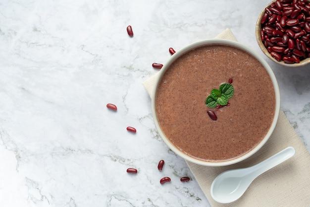 Rode bonen hete soep in witte komplaats op witte marmeren vloer