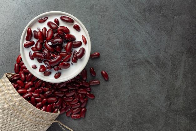 Rode bonen kokosmelk dessert in witte kom naast de zak met rode bonen