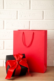 Rode boodschappentas met cadeau op lichte achtergrond. zwarte vrijdag. bovenaanzicht