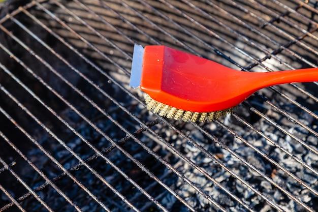 Rode borstel met gouden haren en krabber voor het reinigen van de grill