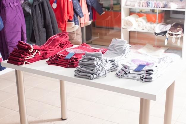 Rode broek die in rijen op de witte plank in een kledingwinkel is gestapeld