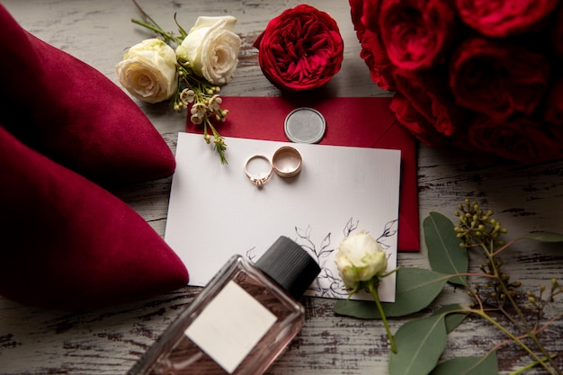 Rode bruiloft. trouwringen op witte en rode uitnodiging dichtbij parfumfles